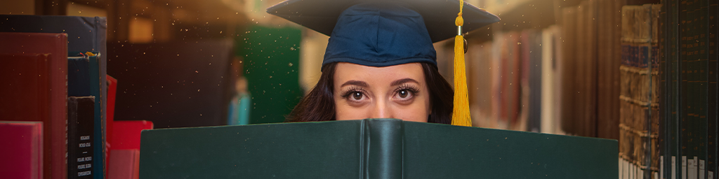 Undergraduate woman student holding a very large book and looking over the top in a library