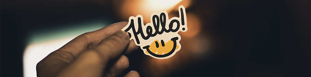 Person holding some paper with the word hello and a smiling face below