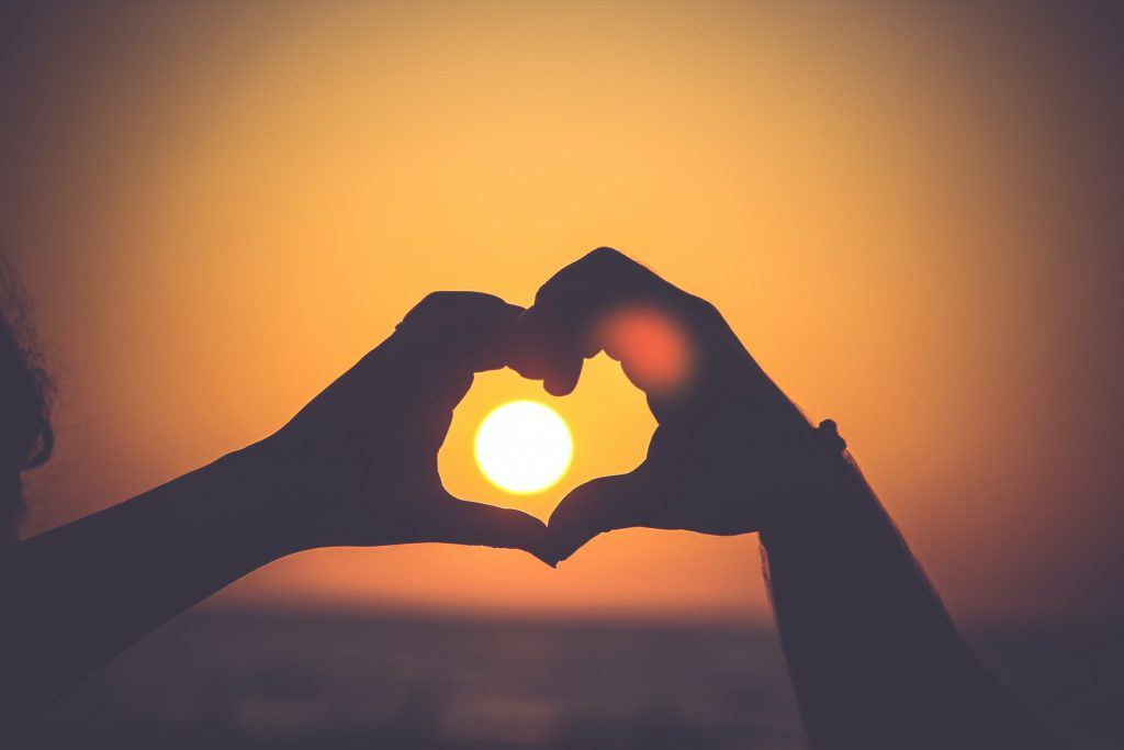 Two hands make the shape of a heart around the sun low in the sky