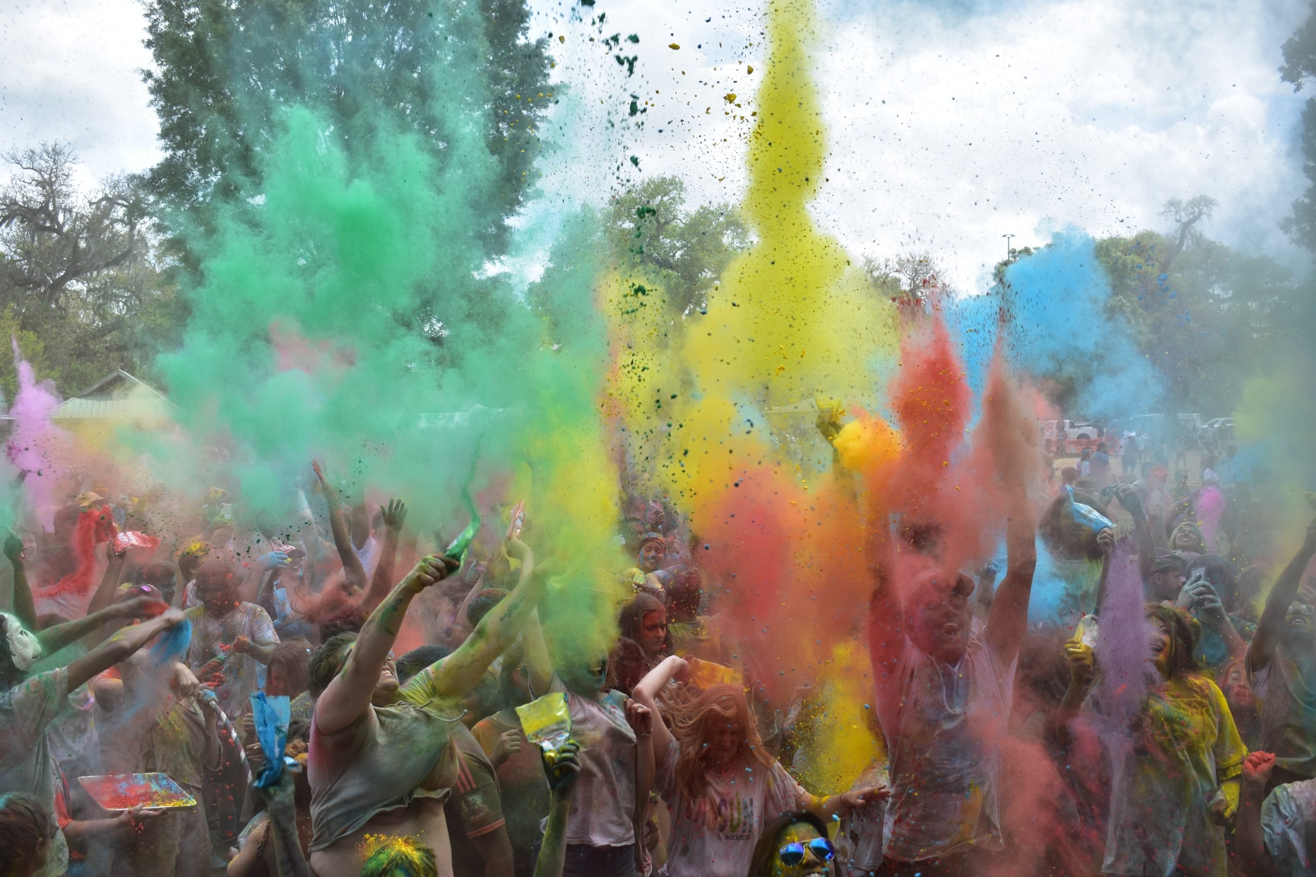 Many people throwing powder pain in a rainbow of colours